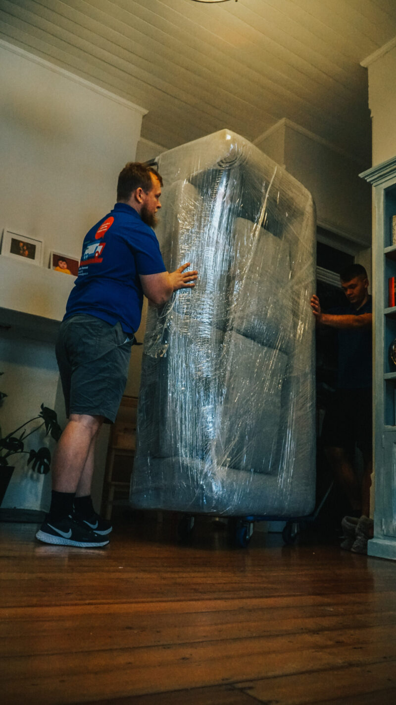 ABC Removalist moving wrapped furniture on dolly